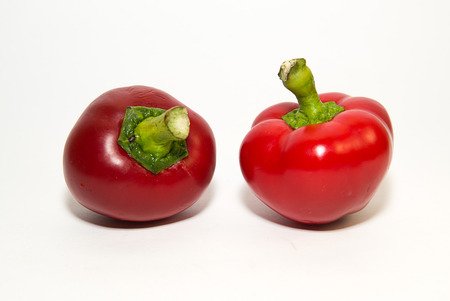 heartiness: Two red peppers on a white background