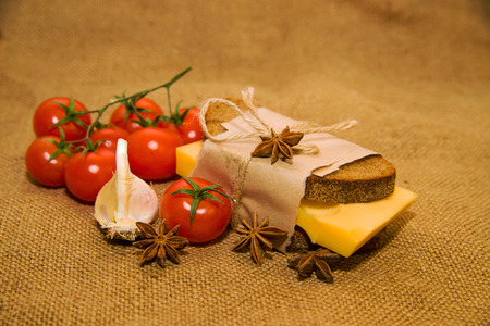 piquancy: Sandwich with cheese wrapped in paper, cherry tomatoes and garlic on old cloth Stock Photo