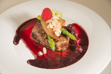 piquancy: Piece of roasted meat in cherry sauce, asparagus,  raspberry on a white plate