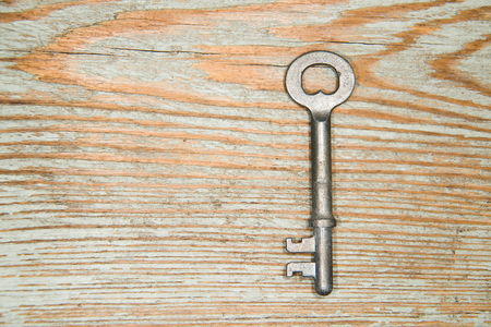 safeness: Vintage key from the lock on a wooden texture