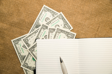 scratchpad: Opened notebook with a blank sheet, pen and money on the old tissue