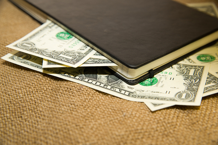 folio: notebook with a blank sheet and money on the old tissue