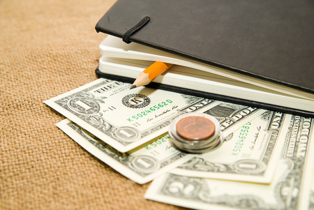 scratchpad: notebook with a blank sheet, pencil and money Stock Photo