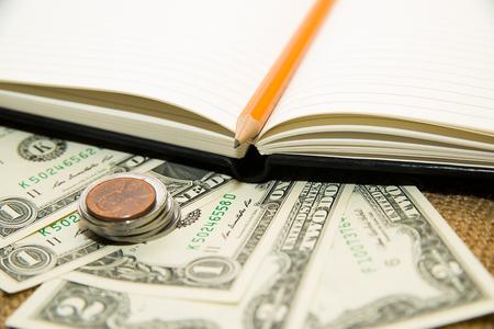maquina registradora: Cuaderno abierto con una hoja en blanco, lápiz y dinero en el viejo tejido Foto de archivo