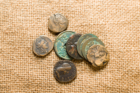 antique coins: Antique bronze coins with portraits of emperosr on old cloth