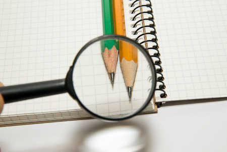 augmentation: The hand with a magnifying glass and two pencils on over white Stock Photo