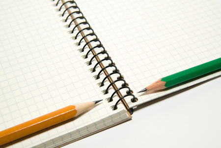 folio: Opened notebook with a blank sheet and pencils on over white