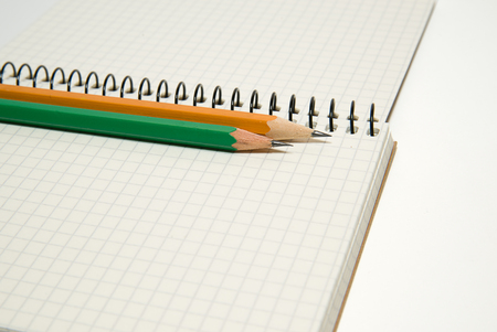 scratchpad: Opened notebook with a blank sheet and pencils on over white