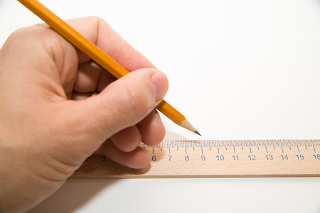 folio: Mens left hand holding a pencil on a white Stock Photo