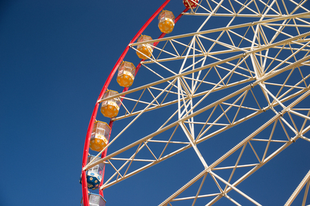 avocation: Atraktsion Ferris wheel against a blue sky with clouds