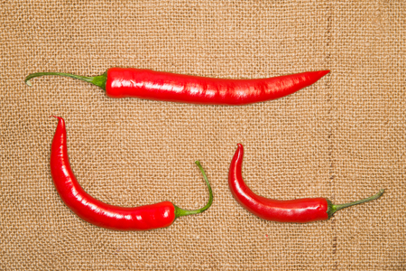 admixture: Three red Chile peppers on old cloth