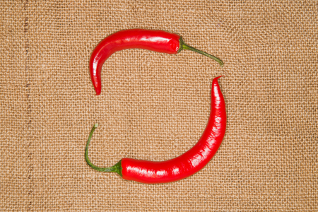 admixture: Two red Chile peppers on old cloth Stock Photo