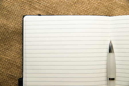 scratchpad: Opened notebook with a blank sheet and pen on the old tissue Stock Photo