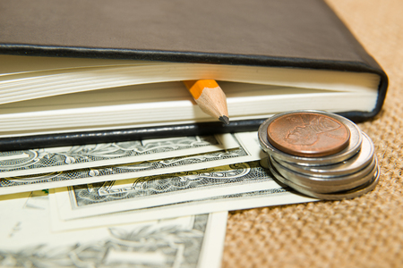 memento: notebook with a blank sheet, pencil and money on the old tissue Stock Photo