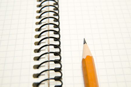 depict: Opened notebook with a blank sheet and pencil on over white