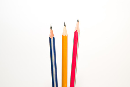 describe: Three pencils of different colors on a white