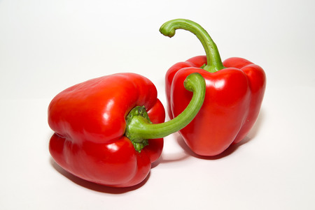 soundness: Two red  peppers on a white background