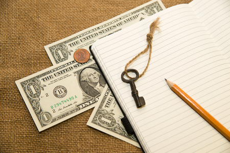 scratchpad: Opened notebook with a blank sheet, pencil, key and money on the old tissue