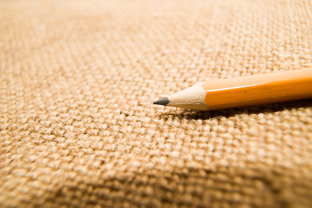 depict: Yellow wooden pencil for drawing on old cloth