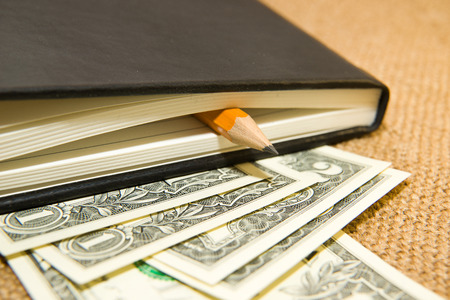 folio: notebook with a blank sheet, pencil and money on the old tissue Stock Photo