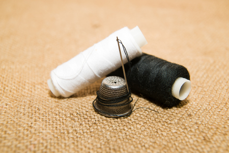 modiste: Sewing Needle, thimble and thread spool on the old cloth