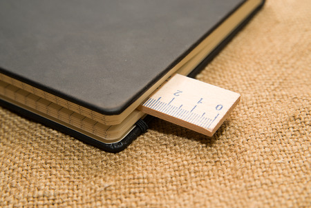 calibre: Notepad with a recording sheet and wooden ruler on the old tissue