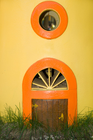 backstop: The little door and  window in a yellow wall