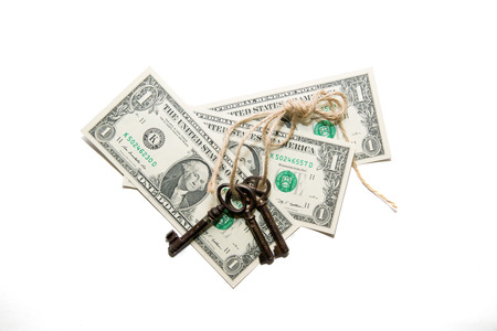 pack string: Keys tied with a rope and a few  dollars banknotes on a white background