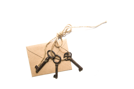 pack string: Three old keys tied with a rope, and envelope on a white background Stock Photo