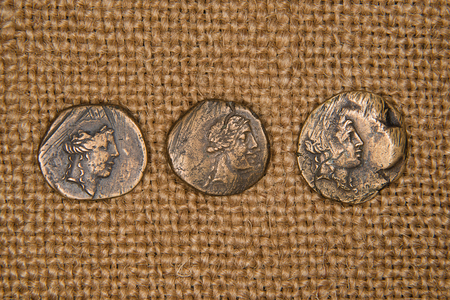 antique coins: Antique bronze coins with portraits of emperors on old cloth