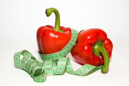 extent: Ripe red peppers and of tailoring meter on over white Stock Photo