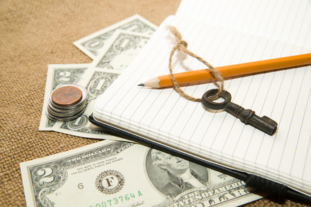 scratchpad: Opened notebook with a blank sheet, pencil and money on the old tissue