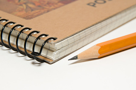 memento: Closed notebook with a blank sheet and pencil on over white