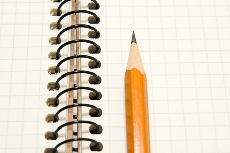 folio: Opened notebook with a blank sheet and pencil on over white