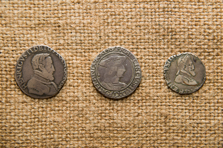 silver coins: A lot of old French silver coins with portraits of kings on the old cloth Stock Photo