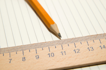 Notepad with a recording sheet, pencil and wooden ruler on the old tissue