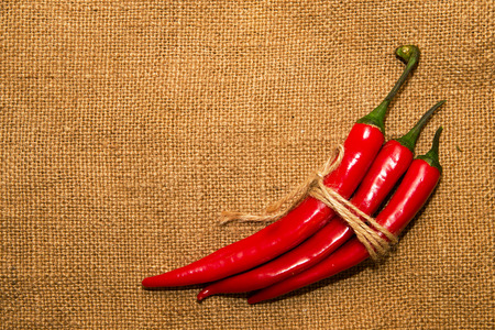 admixture: Three Chile peppers tied with a rope  on old cloth