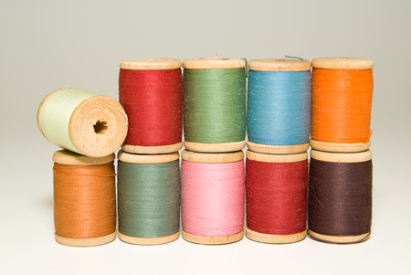 Several spools of thread of different colors on over white