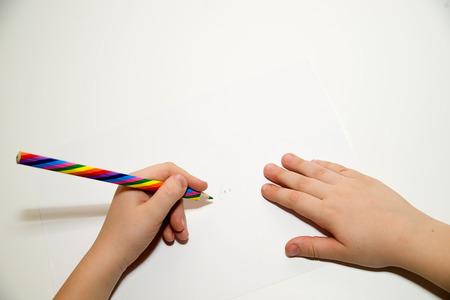 Kid's linker hand met een potlood op een witte