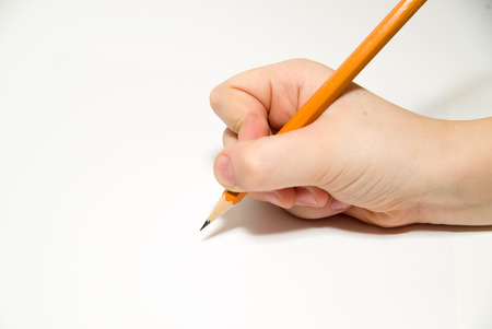 folio: Kids  hand  holding a pencil on a white