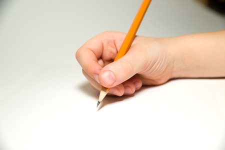 folio: Kids right hand holding a pencil on a white