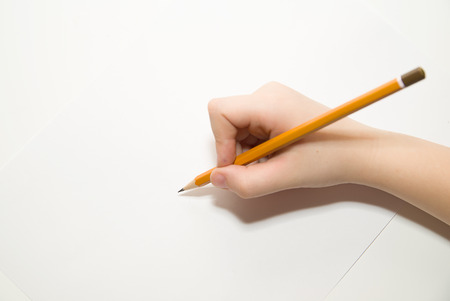 memento: Kids right hand holding a pencil on a white