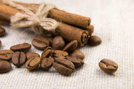 vigor: A lot of roasted coffee beans and cinnamon on the tablecloth Stock Photo