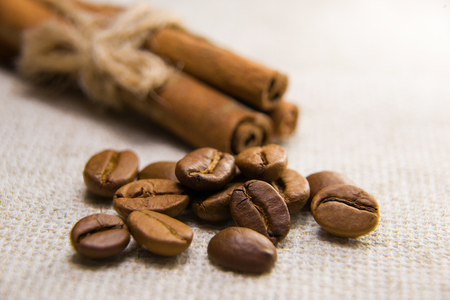 A lot of roasted coffee beans and cinnamon on the tablecloth Stock Photo