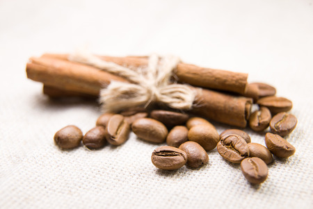 strenuous: A lot of roasted coffee beans and cinnamon on the tablecloth Stock Photo