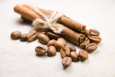 spirited: A lot of roasted coffee beans and cinnamon on the tablecloth Stock Photo