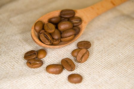 potation: A lot of roasted coffee beans in the spoons