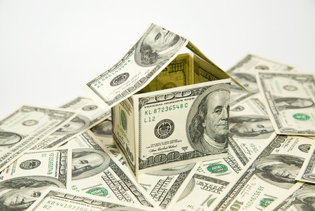 emolument: US dollar banknotes on display in the shape of a house on white
