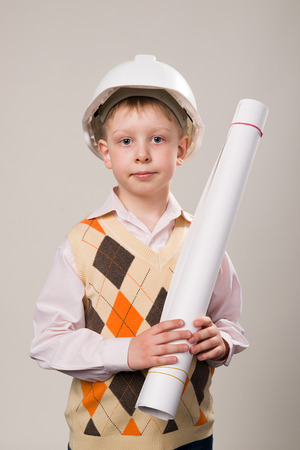 casque: Boy in a white construction helmet holding a drawing
