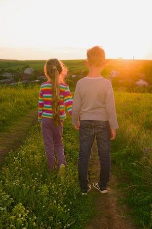 Niño y niña de la mano caminando por la carretera al atardecer